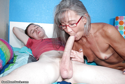 Glasses adorned granny sucks with an increment of tugs exposed to a younger man
