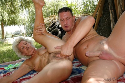 Bosomy granny anent unshaved pussy fucks a youngster alfresco